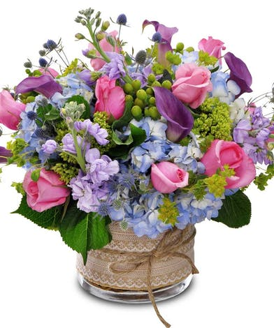Calla lilies, roses and hydrangea in a clear glass vase tied with a rustic bow and lace ribbon.