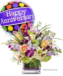 Purple dendrobium orchids, peach roses and green hydrangea in a cube vase accompanied by a happy anniversary mylar balloon.