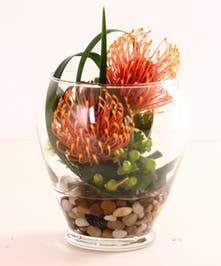 Two pincushion protea, hypericum berries and greenery in a glass vase.
