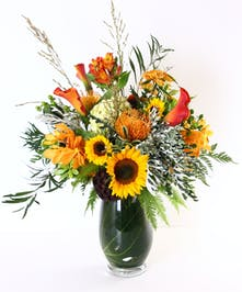 Sunflowers, protea, calla lilies and more in a leaf lined vase.