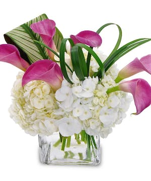 Hydrangea, calla lilies and greenery in a clear glass cube vase.