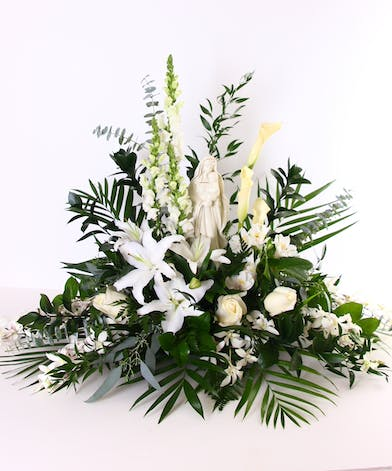 All-white sympathy arrangement with a keepsake statue of the Virgin Mary.