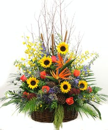 Sympathy arrangement of sunflowers, birds of paradise and roses.
