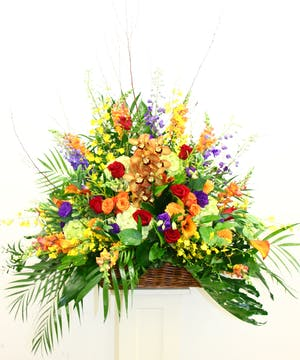 Sympathy basket of orchids, roses, hydrangea and calla lilies in a bright display.