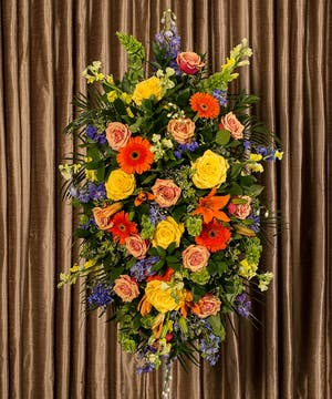 Funeral spray of assorted flowers in bold and bright colors.