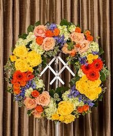 Funeral wreath of assorted flowers in bold colors.
