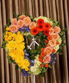 Sympathy heart in yellow, orange, peach, blue and green flowers displayed on an easel.