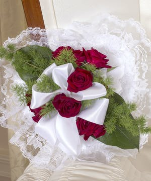 Satin pillow accented with red roses and greenery.