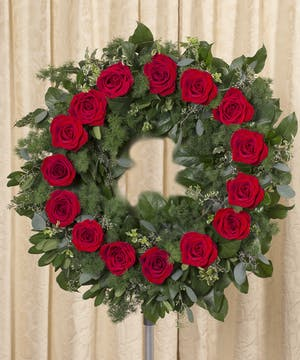 Sympathy wreath of red roses and foliage.