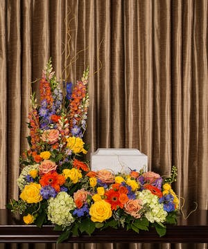 Bright floral tribute to surround a memorial urn.