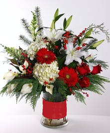 Christmas bouquet of red and white flowers, pine foliage and more in a ribbon-wrapped vase.