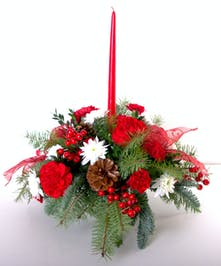 Mixed red and white flowers and holiday trim in a traditional centerpiece with a red taper candle.