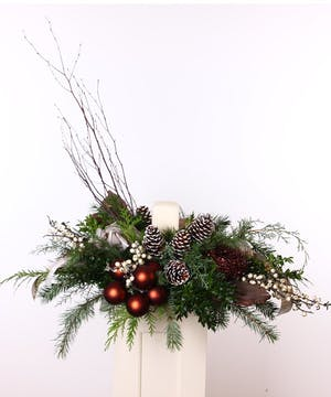 Winter centerpiece with an ivory pillar candle surrounded by berries, pine cones, birch and holiday ornaments