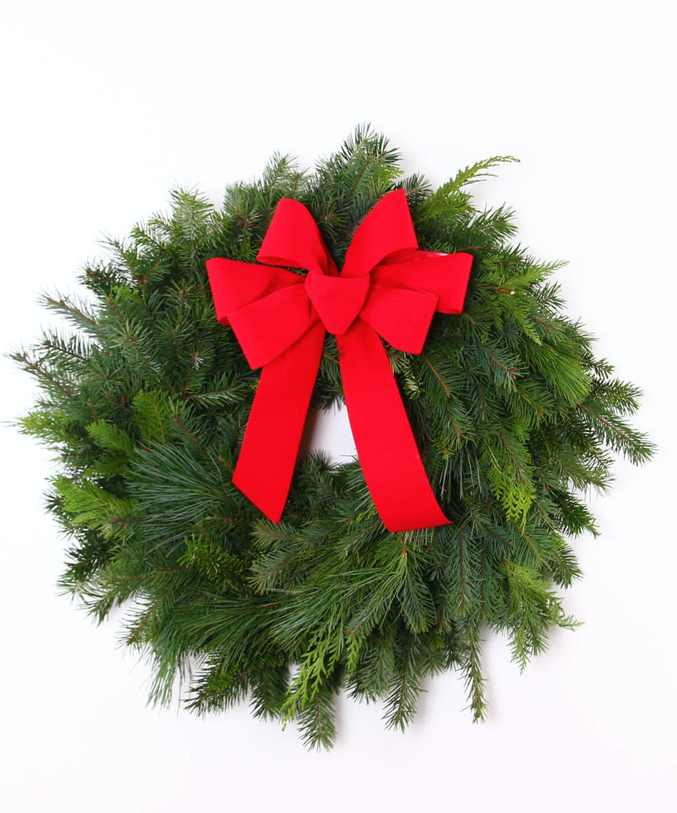 Evergreen wreath of assorted greens topped with a red velvet bow.