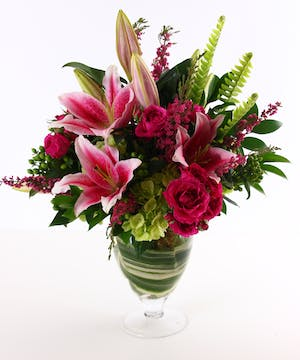 Lilies, roses, and hydrangea in a leaf lined glass vase.
