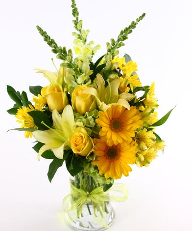 Yellow roses, lilies and daisies in a glass vase.