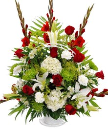 Sympathy arrangement of red and white flowers.