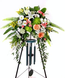 Sympathy spray with a wind chime included and displayed on an easel.