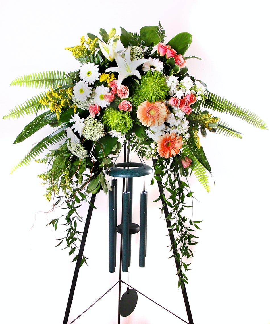 Memorial chime spray funeral flowers in rochester ny sympathy spray with a wind chime included and displayed on an easel izmirmasajfo