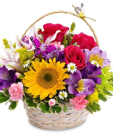Roses, sunflowers and lilies in a basket decorated with butterflies.