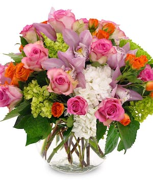 Cymbidium orchids, roses, hydrangea and more in a large bubble bowl vase.