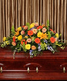 Casket spray of bold and colorful flowers with assorted greenery.