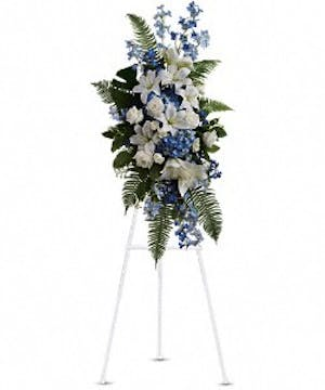 Sympathy spray of blue and white flowers and ferns presented on an easel.