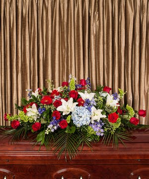 Patriotic casket spray of red, white and blue flowers.