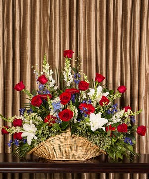 Fireside basket filled with red, white and blue flowers for a patriotic tribute.