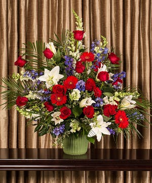 Patriotic arrangement of red, white and blue flowers.