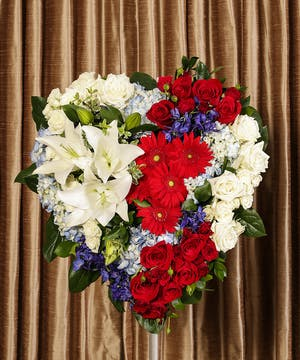 Solid heart in patriotic tribute style made of red, white and blue flowers.