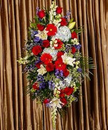Patriotic standing spray of red, white and blue flowers.
