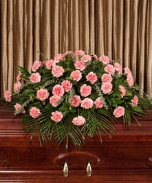 Casket spray of pink carnations and greenery.