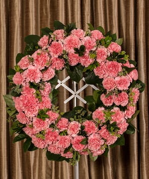 Sympathy wreath of pink carnations and greenery.