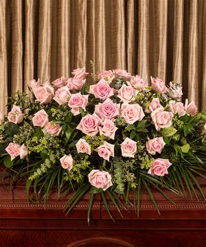Casket spray of pink roses and greenery.