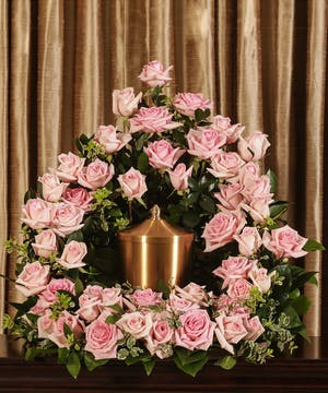 Sympathy display of pink roses to surround an urn.