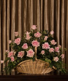 Sympathy basket of pink roses and greenery.