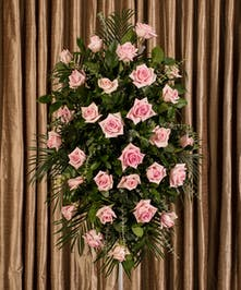 Sympathy spray of pink roses and greenery.