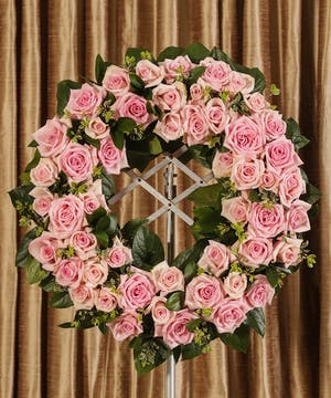 Sympathy wreath of pink roses and greenery.