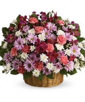Sympathy basket of pastel pink, lavender and white flowers.