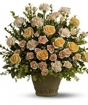 Sympathy spray of peach roses, spray roses and carnations with greenery.
