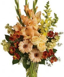 Sympathy arrangement with peach, orange and yellow flowers in a glass vase.