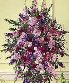 Sympathy spray of purple, red, green and lavender flowers presented on an easel.