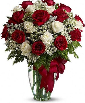 Red and white roses with Queen Anne's Lace in a clear glass vase with a ribbon.