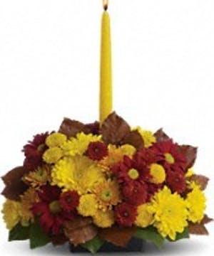 A centerpiece of yellow mums, burgundy flowers and a golden taper candle.