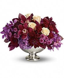 Orchids, roses, hydrangea, dahlias and cushion mums in a mercury glass bowl.