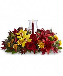Fall centerpiece of orchids, roses, lilies and more with a glass hurricane and taper candle.