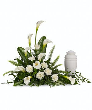 Sympathy arrangement of white calla lilies and roses to accompany an urn, guest book or photograph.