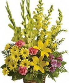Sympathy bouquet of yellow flowers accented with pink carnations.