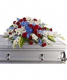 Patriotic casket spray of red, white and blue flowers with greenery.